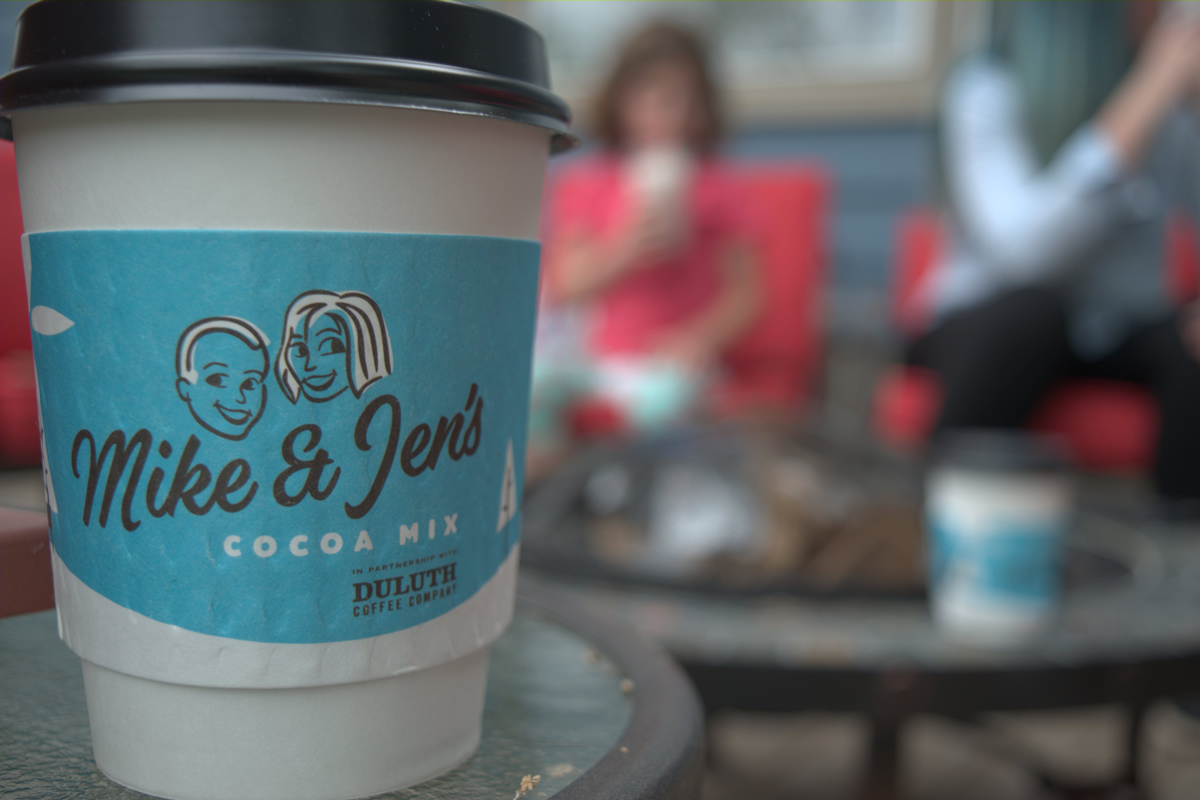 A macro of a paper cup with a Mike & Jen's Cocoa Mix sleeve with people sitting around a campfire