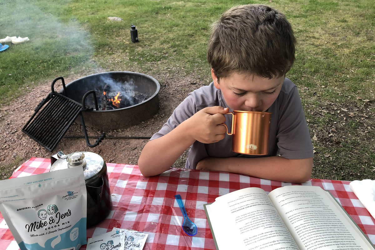 A young boy reading a book and drinking hot cocoa out of a metal mug while outside camping