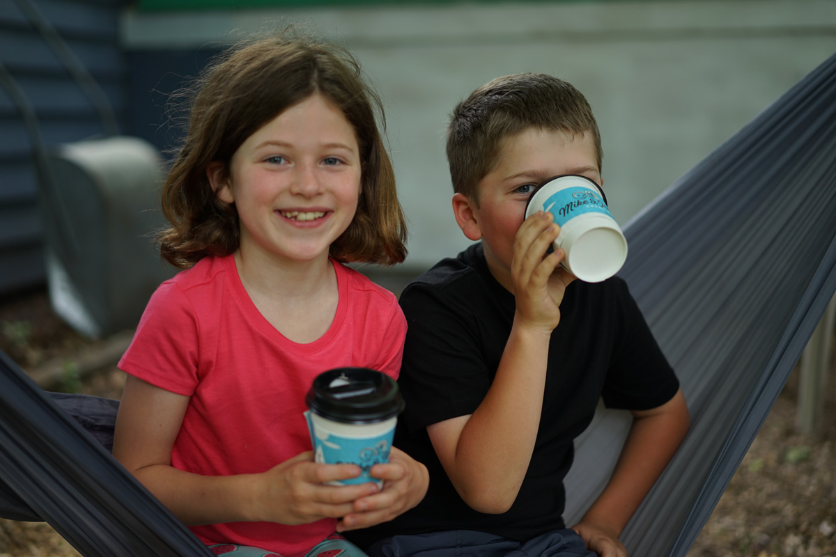 Two smiling kids holding paper cups of Mike & Jen's hot cocoa