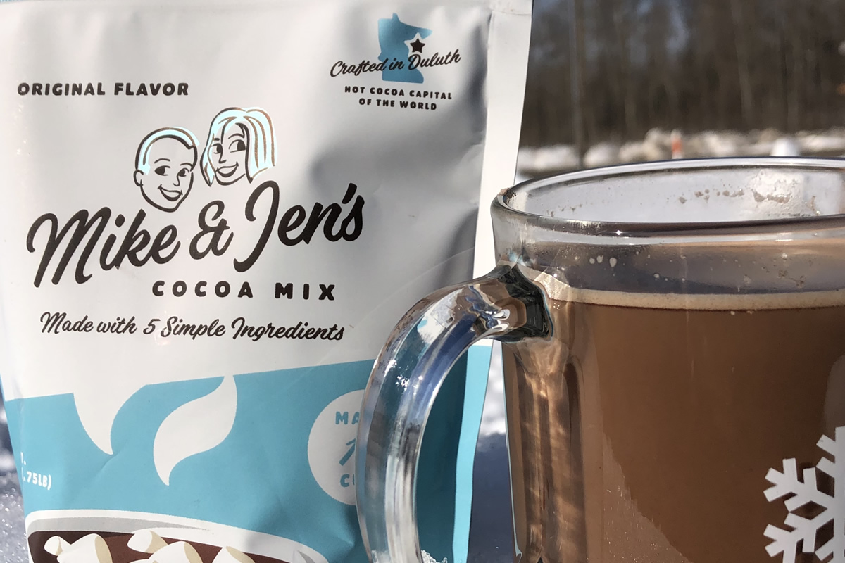 A close up of a 12oz bag of Mike & Jen's Cocoa Mix next to a prepared mug of hot cocoa outside in the snow