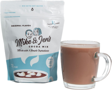 A 12oz bag of Mike & Jen's Cocoa Mix next to a prepared mug of hot cocoa